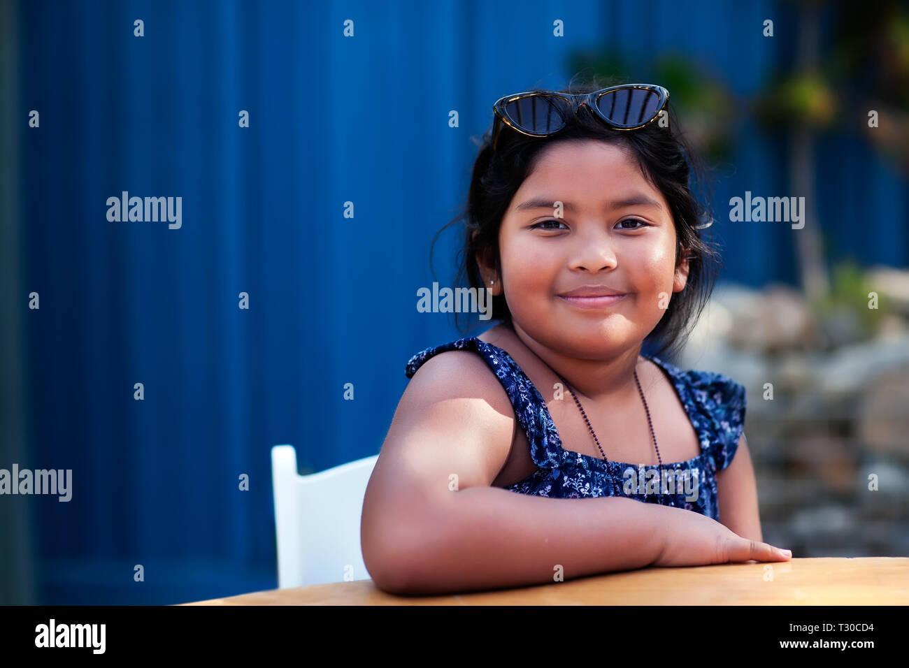 Retrato de una niña amable vistiendo ropa modesta y sombras mientras está sentado y sonriente en un entorno al aire libre. Imagen De Stock