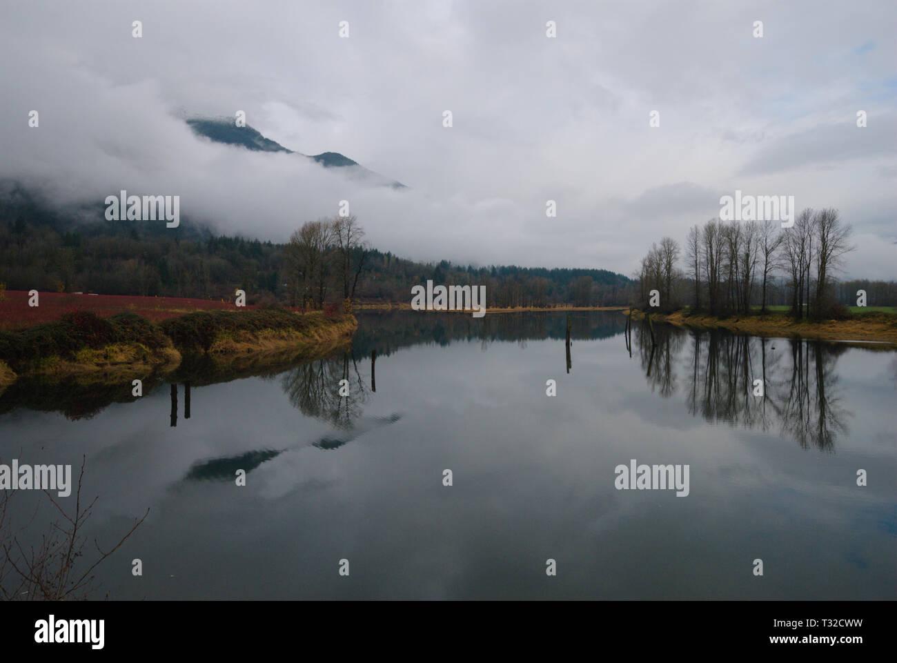Un plácido remanso del Río Vedder refleja un turbulento gris cielo nublado. Foto de stock