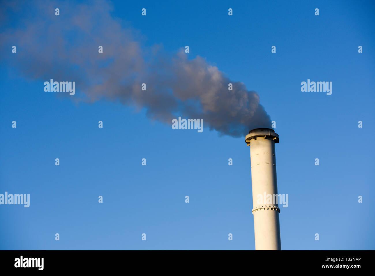 Chimenea calada de humo estaba bombeando fuera el humo negro de la contaminación. Foto de stock