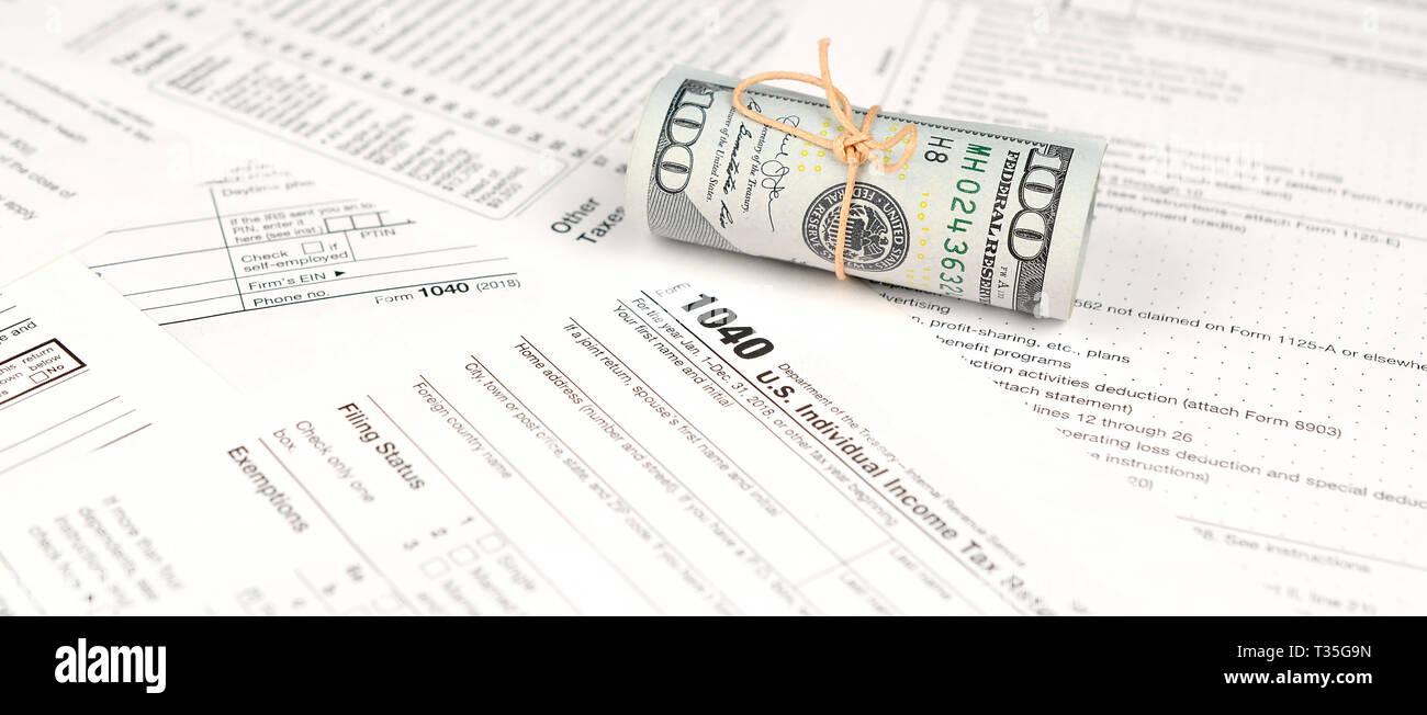 1040 Formulario de devolución de impuestos sobre la renta de las personas físicas con el rollo de billetes de dólar americano cerca. Concepto de período fiscal en Estados Unidos Foto de stock