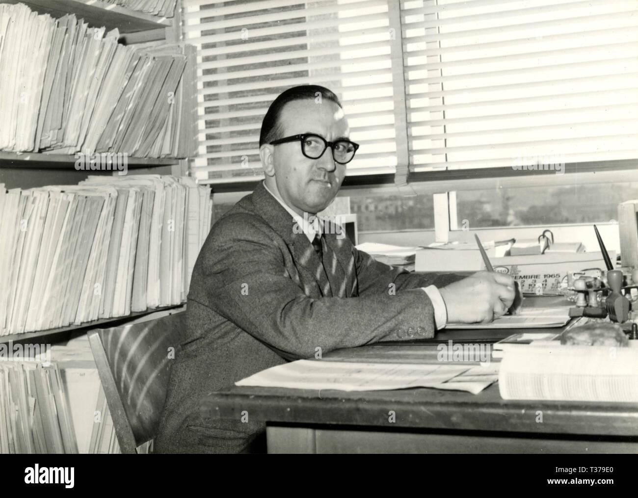Un empleado en su escritorio con papeles, Italia 1965 Imagen De Stock