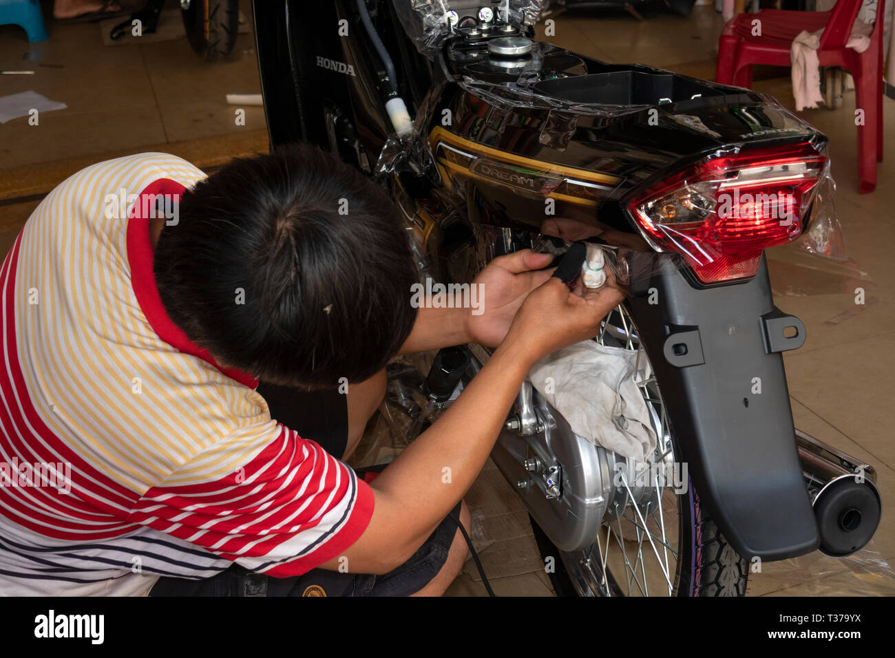 Camboya, Kampong (Kompong Cham), del centro de la ciudad, motocicleta showroom hombre aplicar calcas personalizadas a Honda Dream moto Foto de stock
