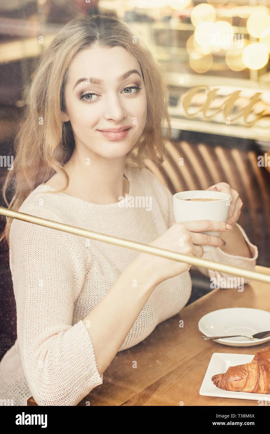 a542df71b Retrato de hermosa niña bebe café y mirando a través de la ventana mientras  estaba sentado en el acogedor café francés. Mujer joven beber té en vintage  ...