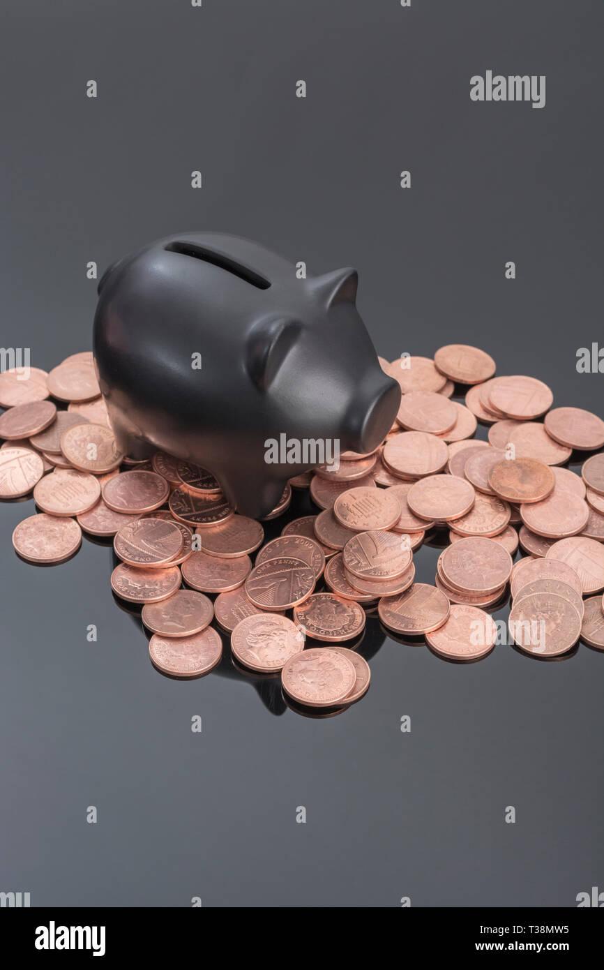 Hucha de cerámica negra con monedas británicas sobre fondo negro reflectante. Metáfora para ahorrar dinero, los ahorros personales, Ahorrar centavos, British pennies. Foto de stock