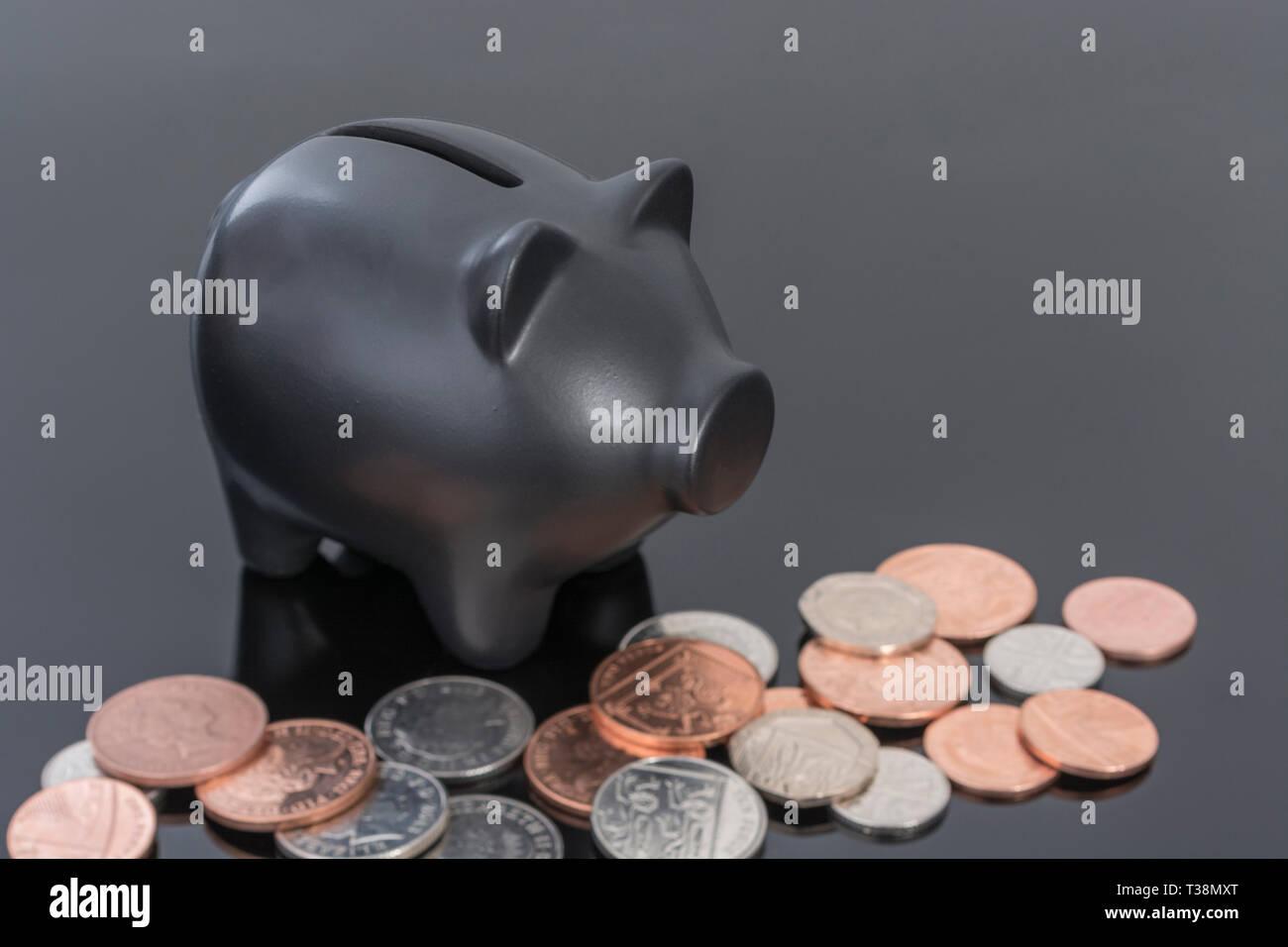 Hucha de cerámica negra con monedas británicas sobre fondo negro reflectante. Metáfora para ahorrar dinero, los ahorros personales. Foto de stock