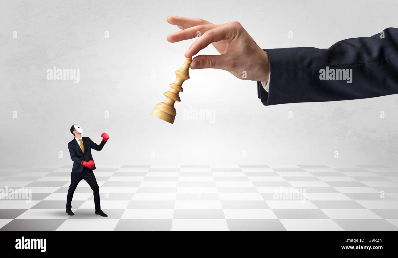 Pequeño Empresario luchando contra la gran figura de ajedrez en una gran mano con tablero de ajedrez concepto Imagen De Stock