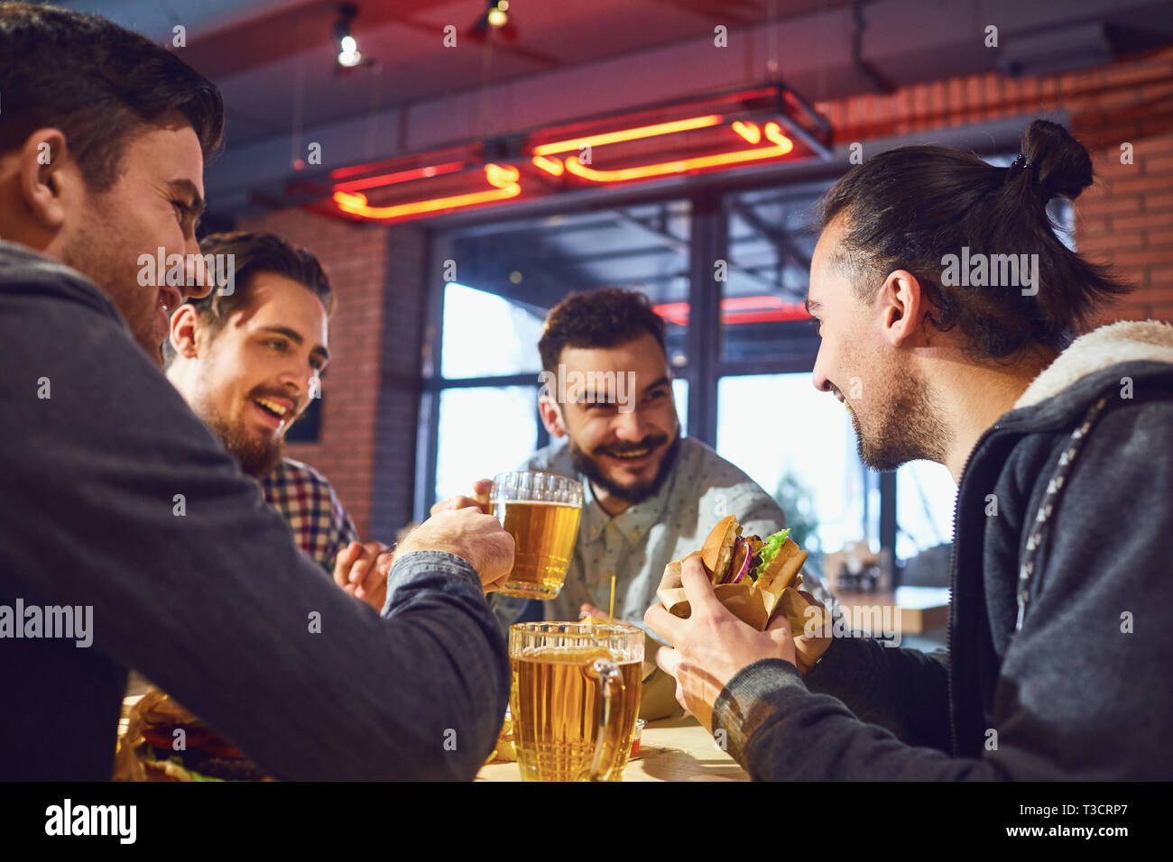 Feliz amigos comer hamburguesas, beber cerveza en un bar. Foto de stock