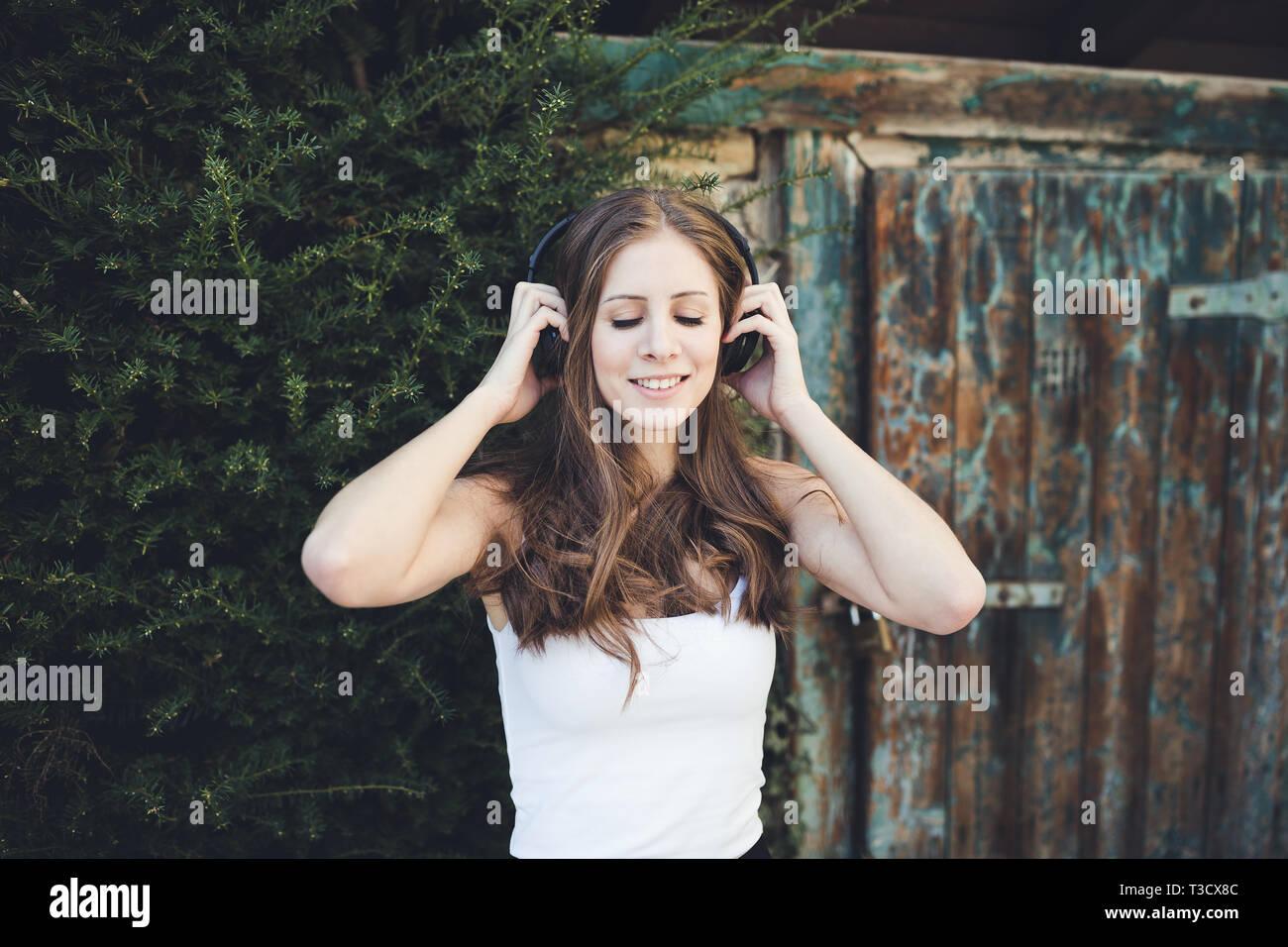 Mujer joven en una camiseta blanca sonriente con los ojos cerrados y escuchar música a través de auriculares al aire libre, campo. Foto de stock