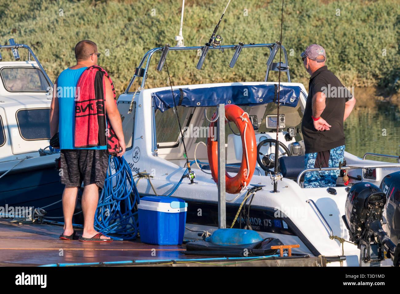 2 hombres de mediana edad charlando de pie en un barco, sugiriendo que tenían intereses similares. Canotaje en el estilo de vida. Imagen De Stock