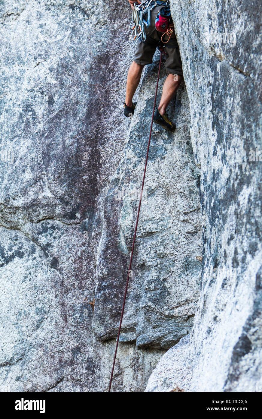 Un hombre escalador ejecuta (subiendo un largo camino sin proteger la posible caída) en el pequeño fume Bluffs área de escalada, Squamish, BC. Foto de stock