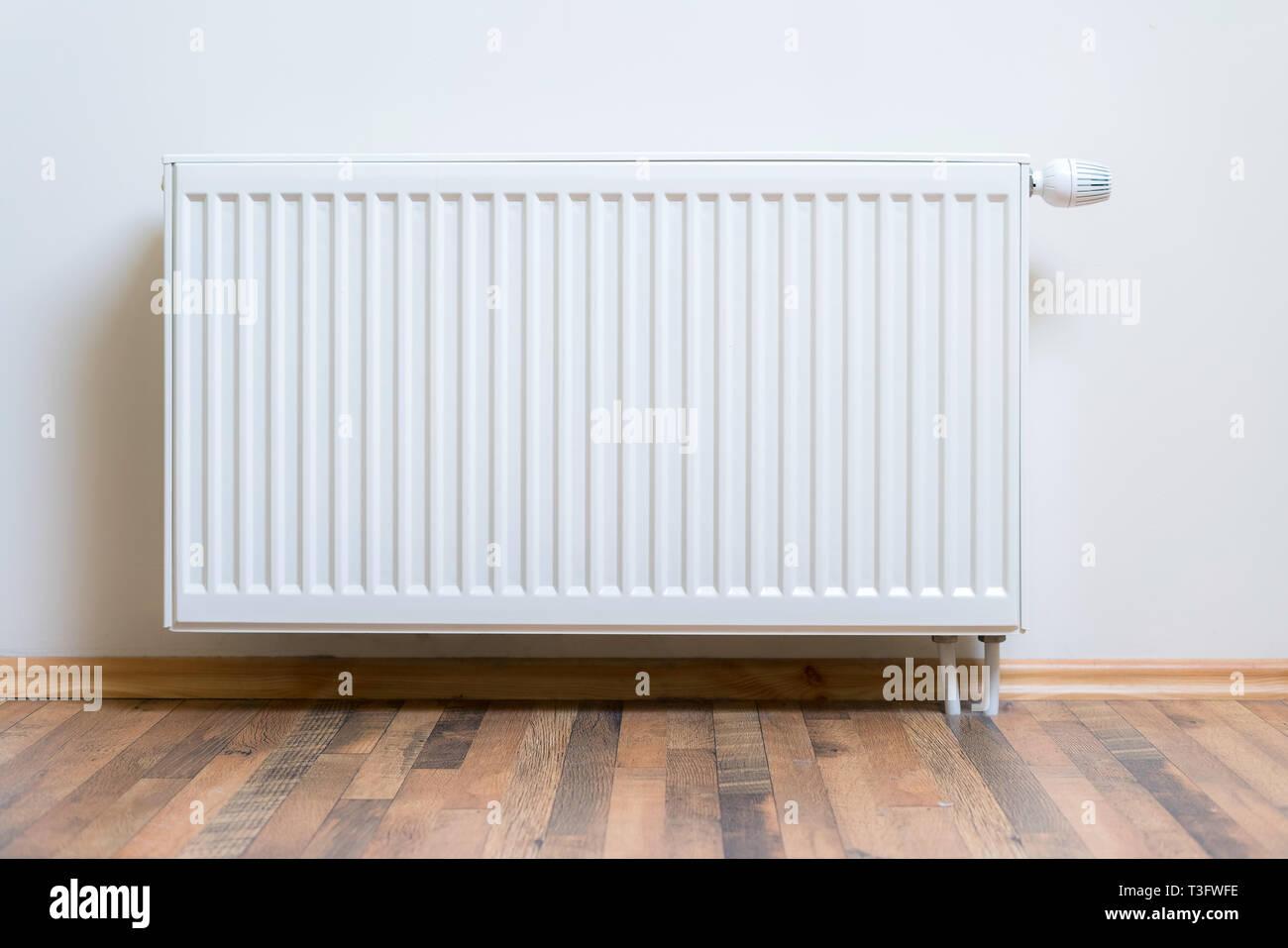 Radiador calefacción en casa en la pared blanca en el suelo de parquet de madera. Equipo de calentamiento ajustable por apartamento y hogar Imagen De Stock