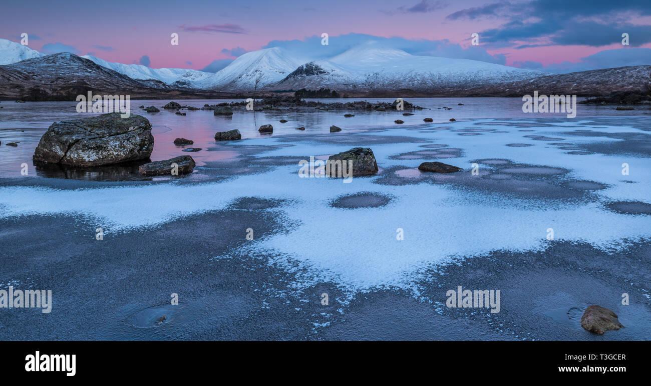 Amanecer sobre un congelado Lochan na h-achlaise sobre Rannoch Moor, cerca de la entrada a Glencoe en las Highlands escocesas Foto de stock