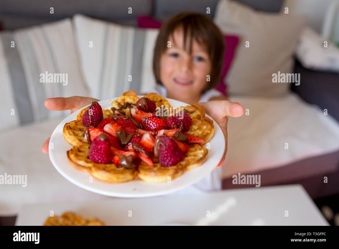 Dulce niño cumpleaños comiendo gofre belga con fresas, frambuesas y chocolate en casa Foto de stock