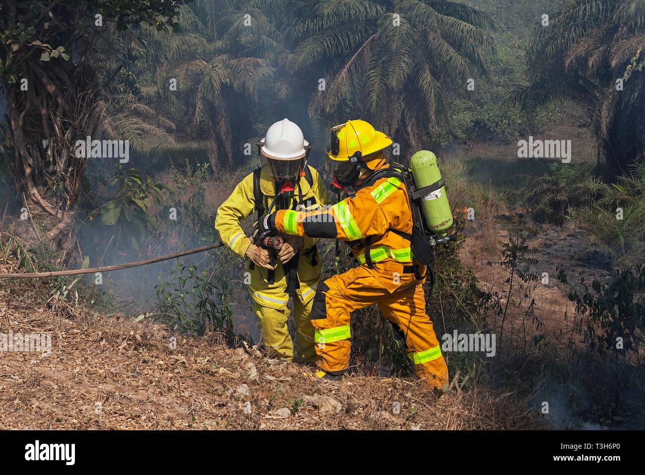 En Sierra Leona la formación del equipo de respuesta de emergencia en la lucha contra incendios hacer pausas entre incendios forestales locales y comunidad con instructor Foto de stock