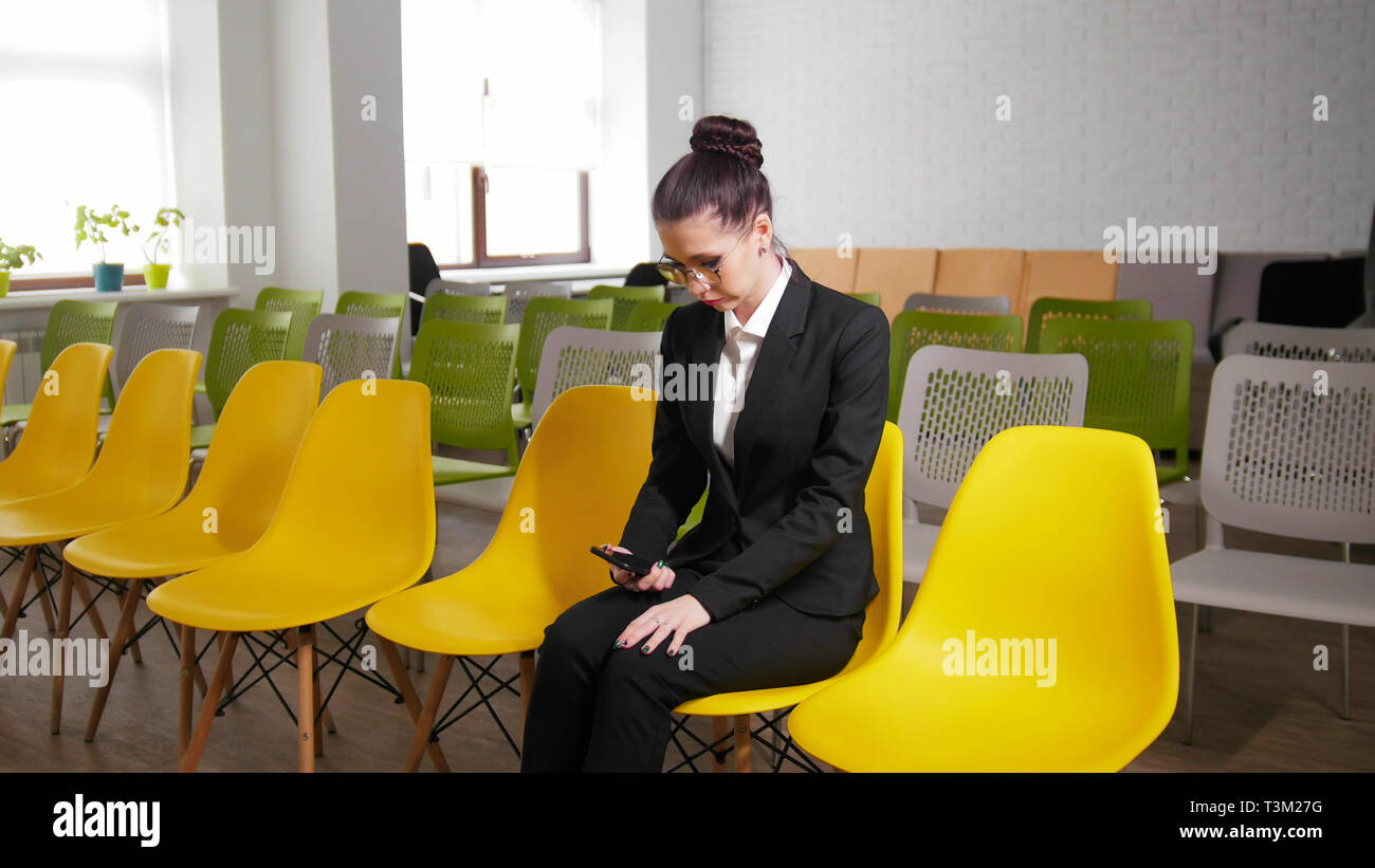 Concepto de negocio. Una mujer sentada en el centro de negocios y nervioso antes de la entrevista la celebración de un teléfono Imagen De Stock