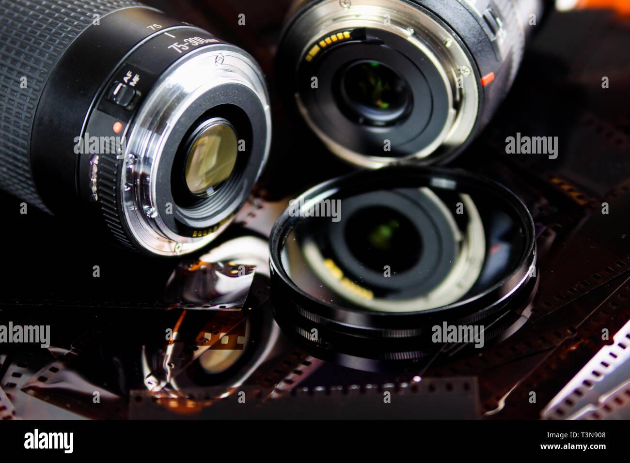 Cerca de dos lentes de cámara con filtro circular aislado de tiras de película negativas Foto de stock