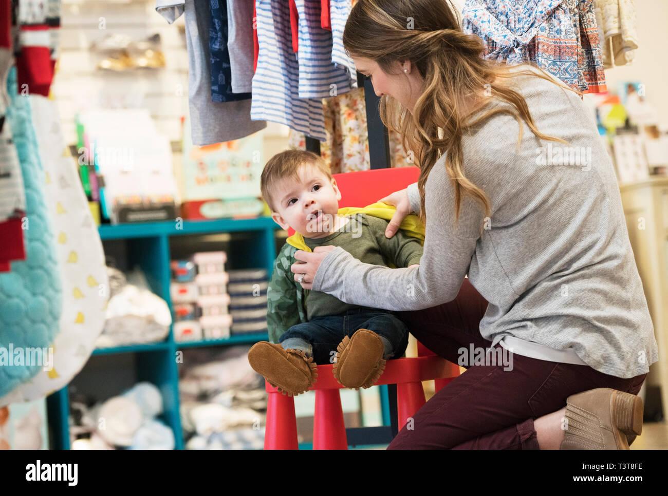 5bd7363a3 La madre y el bebé caucásica hijo de compras en la tienda de ropa Imagen De