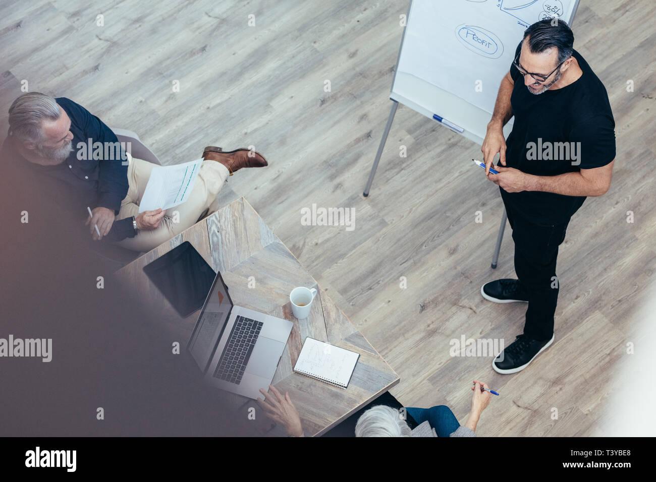Empresario maduro presenta sus ideas sobre la pizarra a los colegas. Manager dando presentación a su equipo en la sala de conferencias en la oficina. Foto de stock