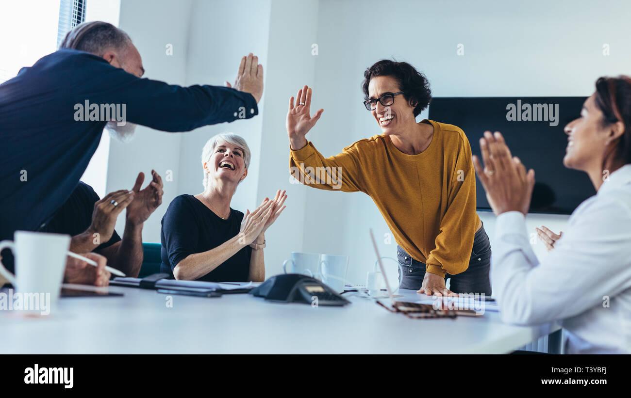 La gente de negocios, dándole a cada otros cinco altos y las palmas. Equipo empresarial celebrando el éxito. Foto de stock