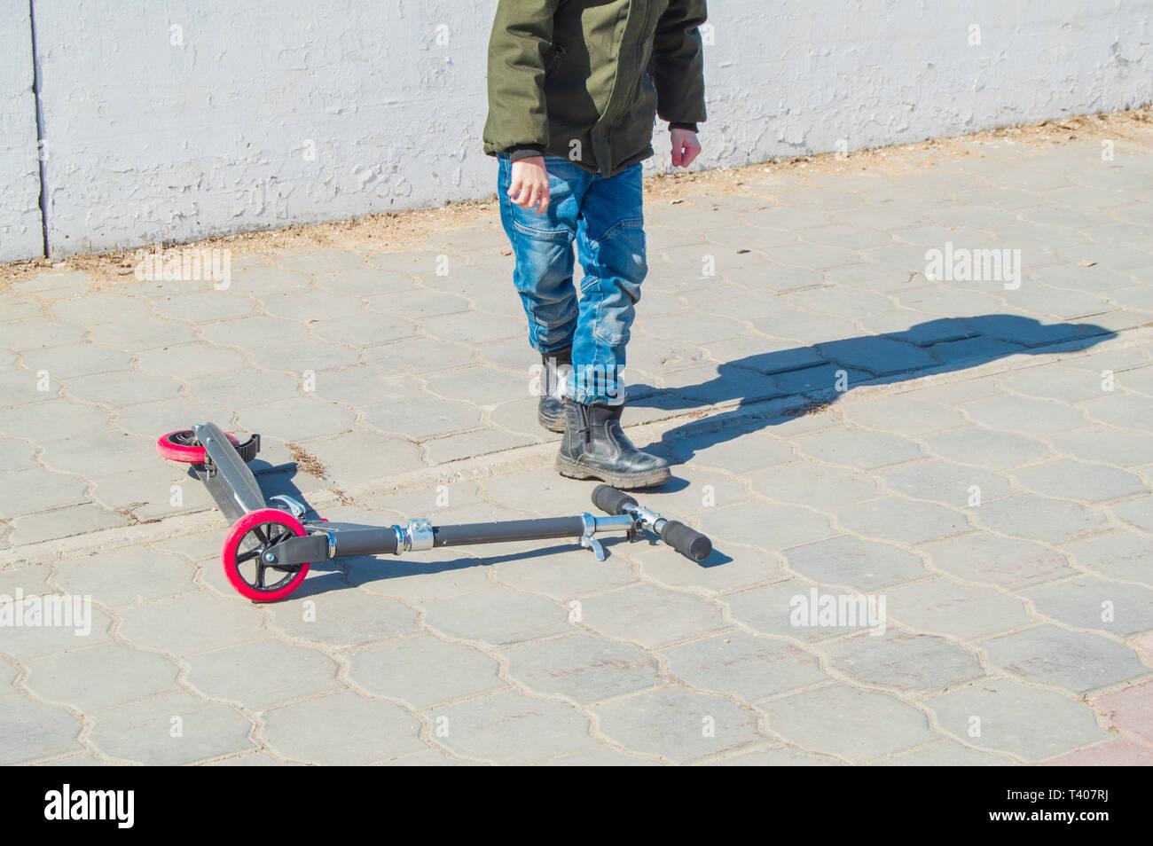 Jovencito En Una Chaqueta Verde Y Pantalones Vaqueros Levanta Su Scooter Despues De Una Caida En El Abierto En El Parque De Entretenimiento Para Ninos En El Aire Fresco Fotografia De Stock