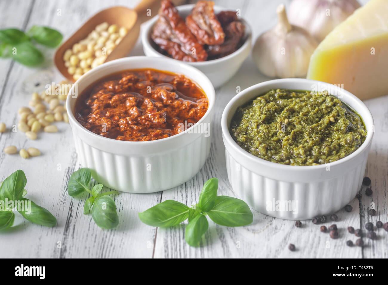 Cuencos de clásico y pesto de tomates secados al sol con ingredientes sobre el fondo blanco de madera Foto de stock