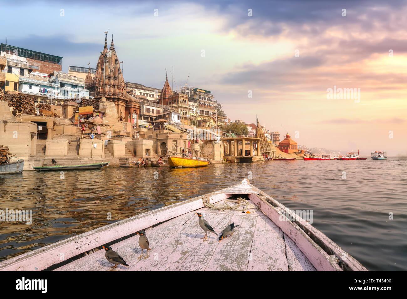 La India antigua arquitectura de la ciudad de Varanasi, visto desde un barco en el río Ganges con vista de las aves migratorias con moody sunset sky Imagen De Stock