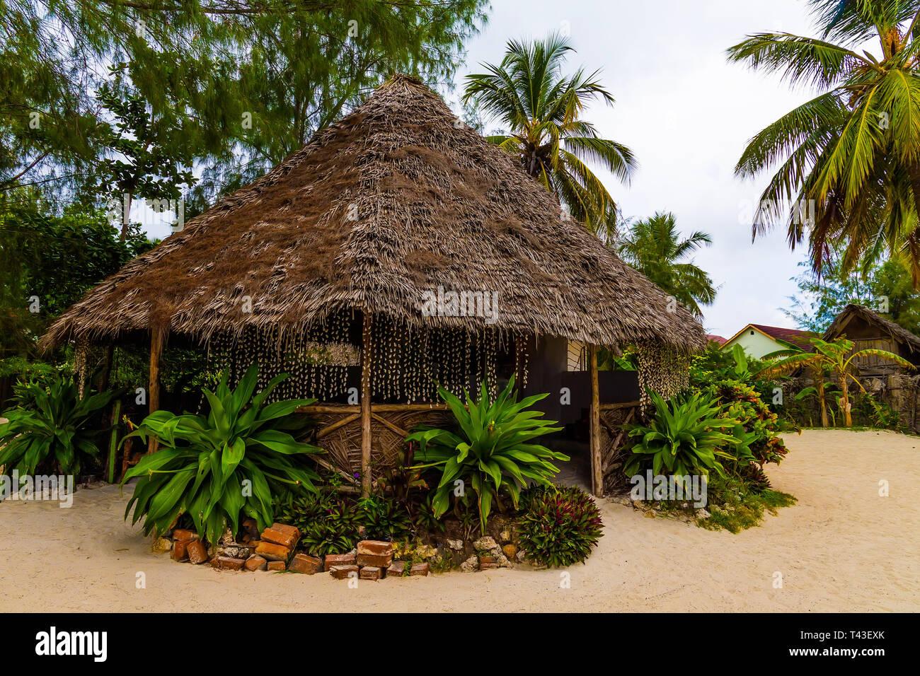 Arbor de paja en la playa de la arena blanca y palmeras verdes alrededor. Foto de stock