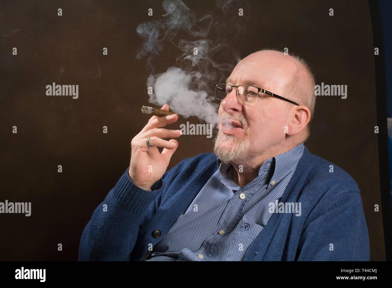 Un hombre de edad avanzada disfrutando de fumar un buen puro Foto de stock