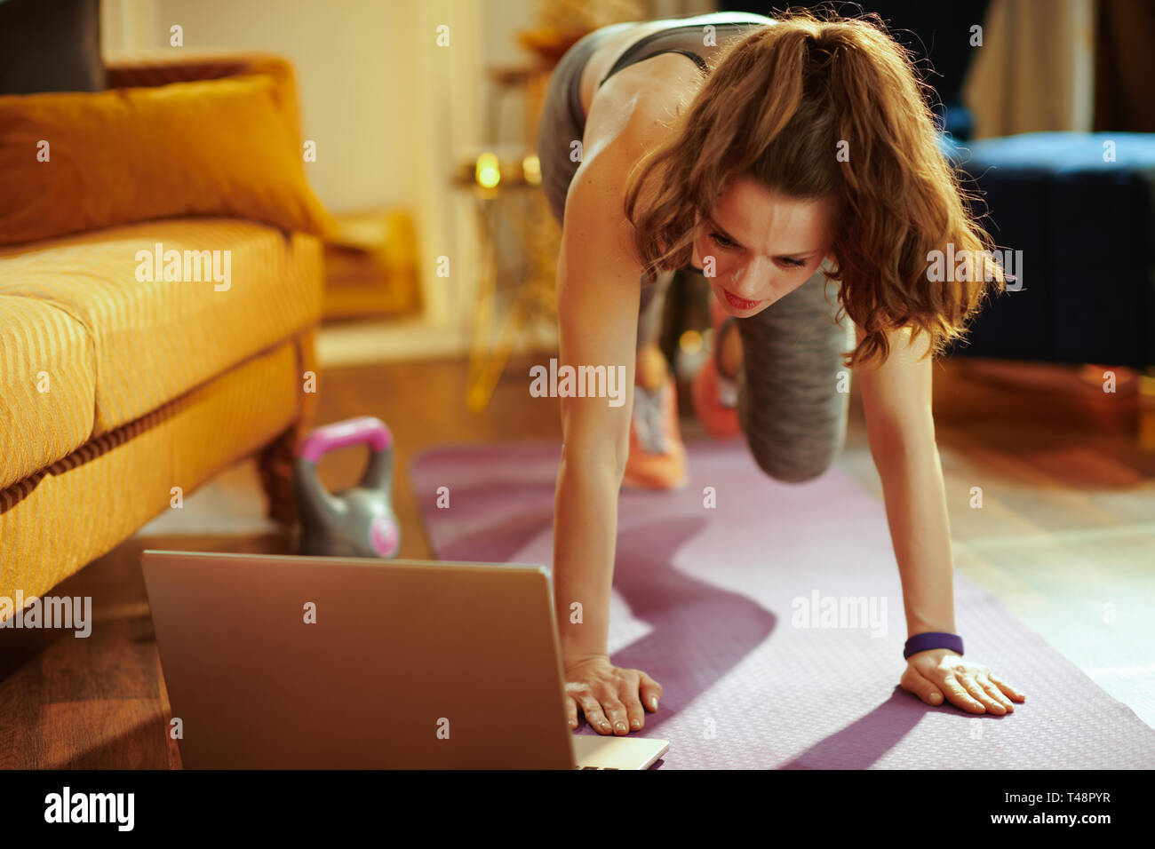 Deportes joven mujer en ropa de gimnasia en casa moderna mediante streaming en línea sitio de fitness en el ordenador portátil y realizar circuitos de entrenamiento en fitness mat. Imagen De Stock