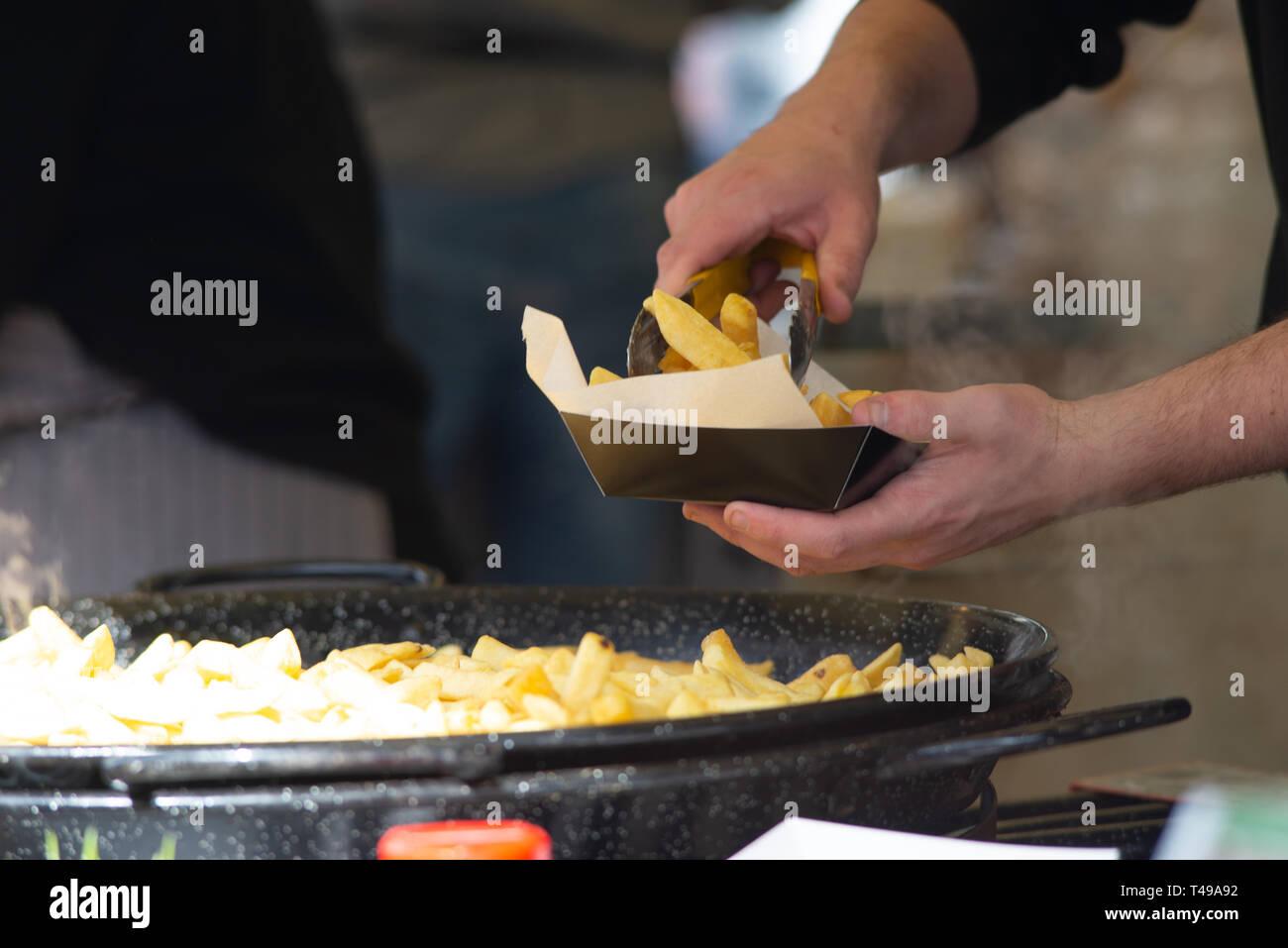 Hombre sirviendo chips en papel absorbente y caja Imagen De Stock