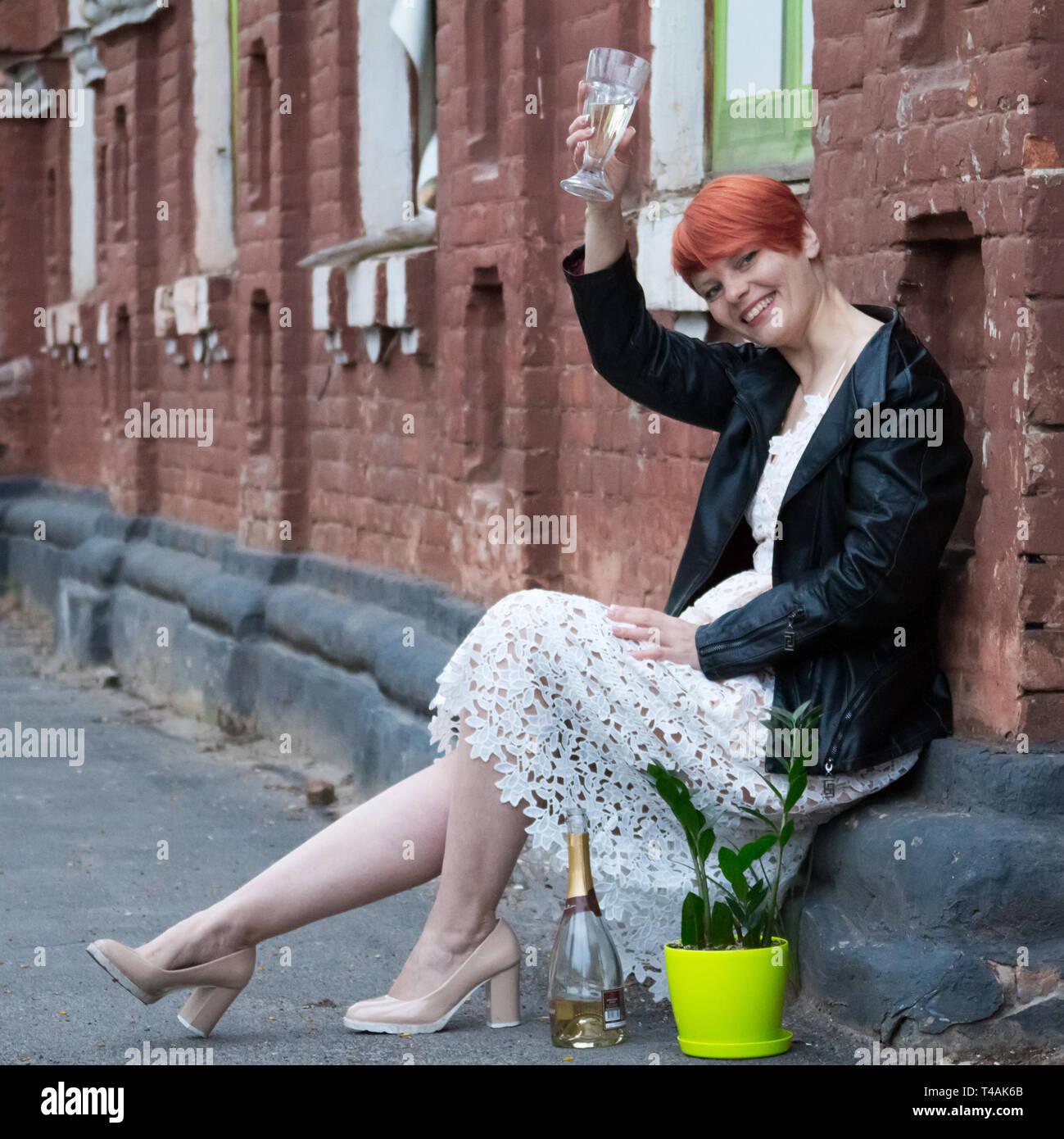 Una joven pelirroja mujer en un vestido blanco se ubica en la calle junto a la planta y brindis con una copa de champán, sonriente, feliz, vacaciones positiv Imagen De Stock