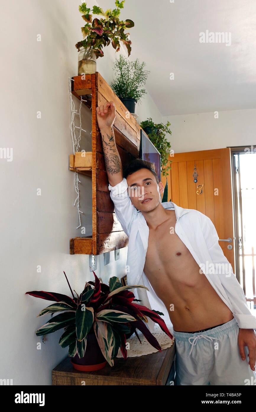 Un joven entre las edades de 21 y 29 está de pie, con su brazo extendido sobre un soporte de madera, y se encuentra entre el follaje de su casa. Foto de stock