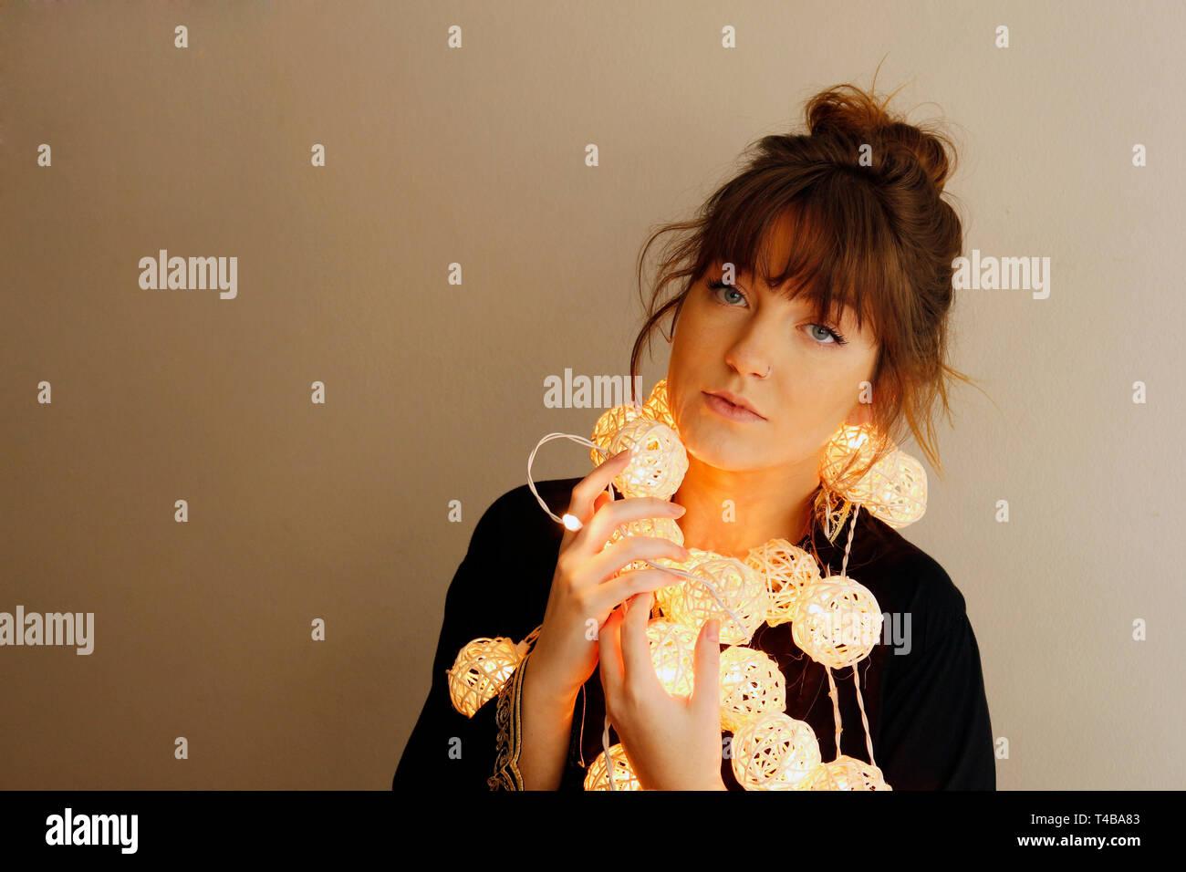 Una jovencita juega con bolas de luces junto a su cara. Parece grave en la cámara. Ella es muy hermosa y muy potente. Imagen De Stock