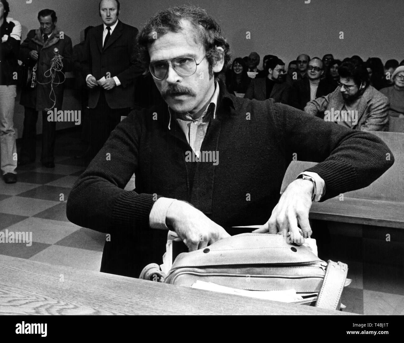 El escritor Günter Wallraff en el banquillo de los acusados antes de la audiencia en la corte comienza el 10 de diciembre de 1975. El escritor y autor de Colonia de 'informes' indeseables, Günter Wallraff (33), tenía que responder a cargos en el tribunal de magistrados de Colonia el miércoles, 10 de diciembre de 1975. Las acusaciones de la fiscalía a él con la falsificación de documentos y uso indebido de documentos de identidad. Con un nombre equivocado, Wallraff había trabajado como mensajero en la preocupación de seguros Gerling en Colonia en 1973. Él había autorizado a sí mismo con tarjetas de seguro de pensiones por invalidez y bajo su nombre equivocado y publicó sus experiencias más adelante en la b Foto de stock