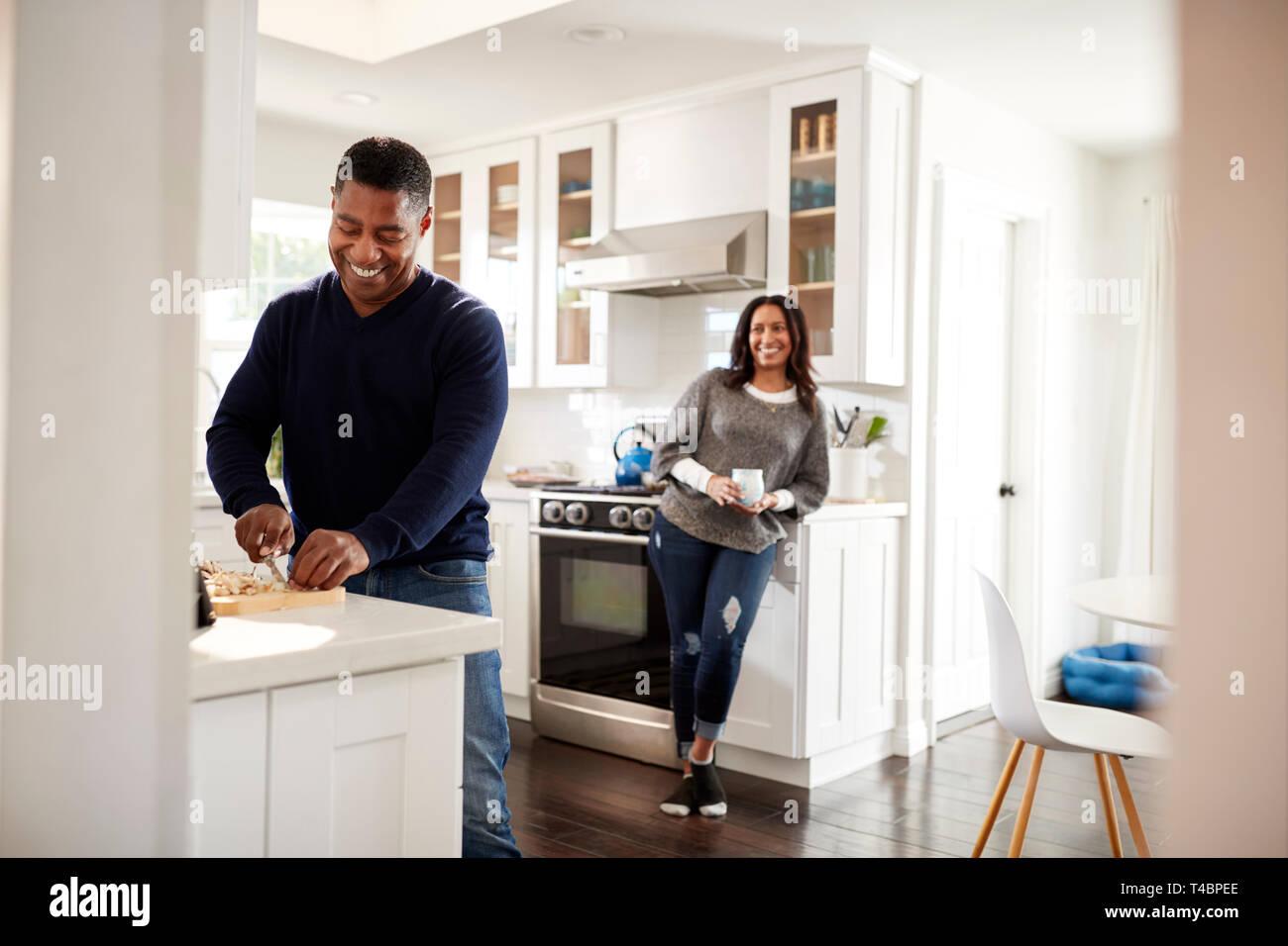 Un varón de mediana edad de pie en la encimera en la cocina preparando la comida, su compañero recostado en el mueble de cocina detrás de él hablando, el enfoque selectivo Foto de stock