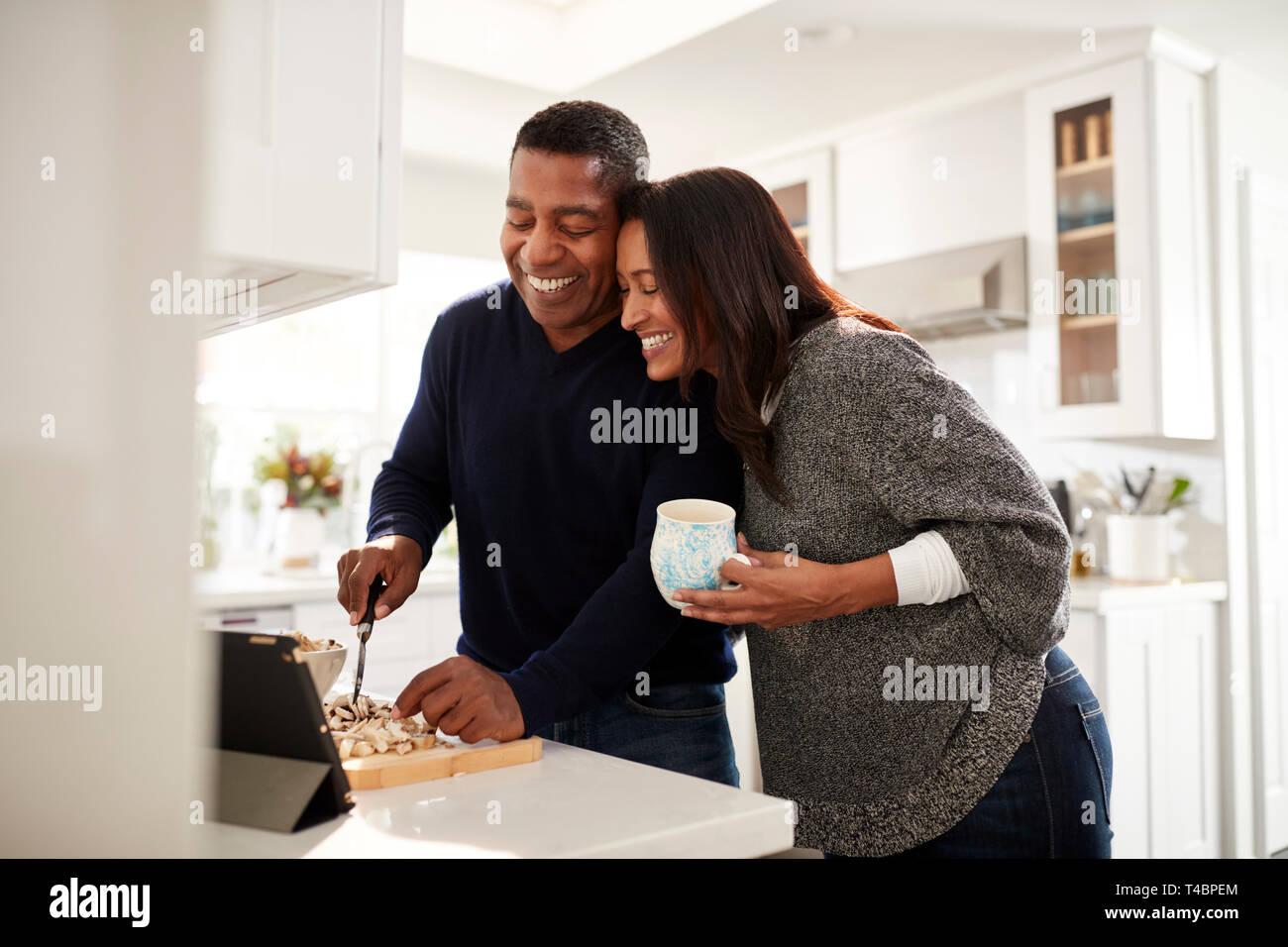 Pareja de mediana edad de raza mixta de pie en la encimera en la cocina preparando los alimentos siguiendo una receta en un tablet pc, el enfoque selectivo Foto de stock