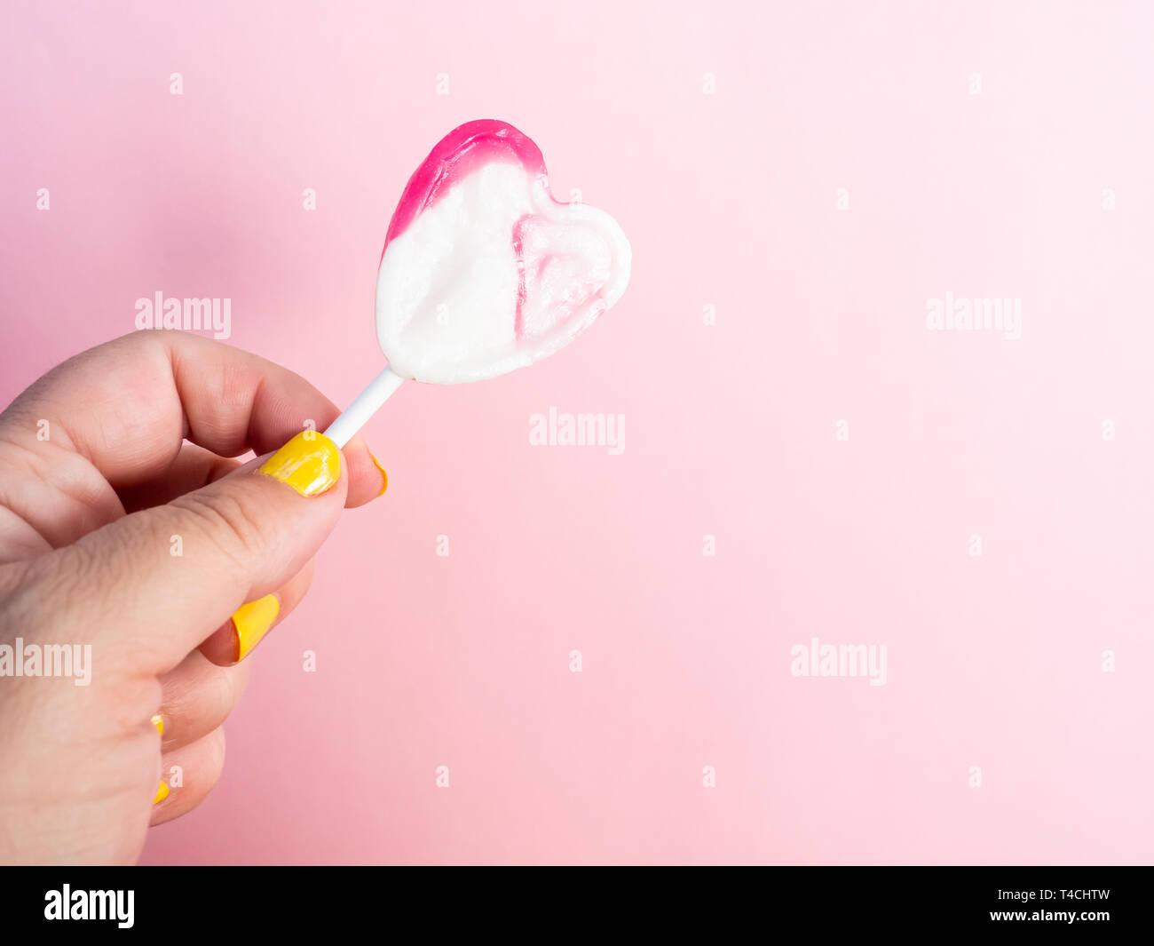 Una Mujer Con Las Uñas Pintadas En Amarillo Con Un Lollipop