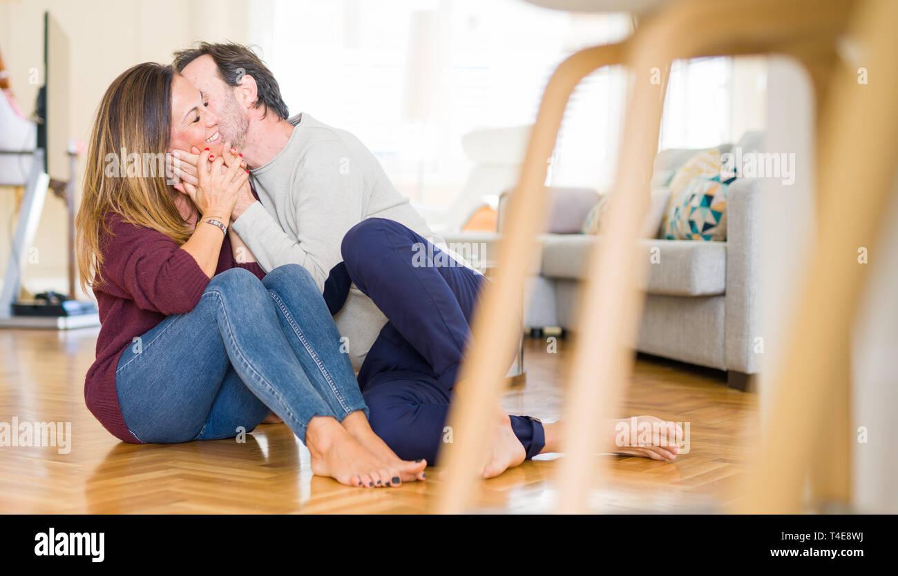 Hermosa pareja romántica sentados juntos en el suelo besándose en el amor en el hogar Foto de stock