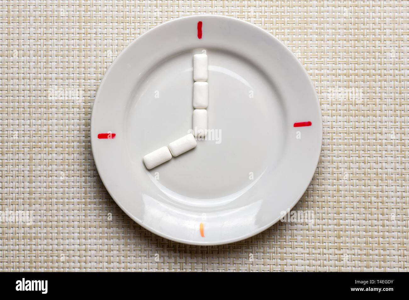 Limpieza de los dientes de la rotura. Tiempo para el cepillado de dientes durante el trabajo o comer. Símbolo de reloj en la placa. Concepto de higiene bucal con pasta de dientes, toothbru Foto de stock