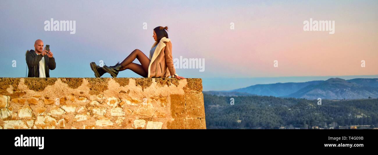 Caravaca, España, 7 de enero de 2019: pareja de turistas tomando fotos en el precipicio de Caravaca castillo en España. Imágenes peligrosas. Fotos arriesgadas en los acantilados. Foto de stock
