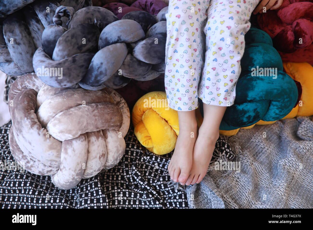Las piernas del niño en pijama junto a inusual almohadas multicolores. Closeup. Foto de stock