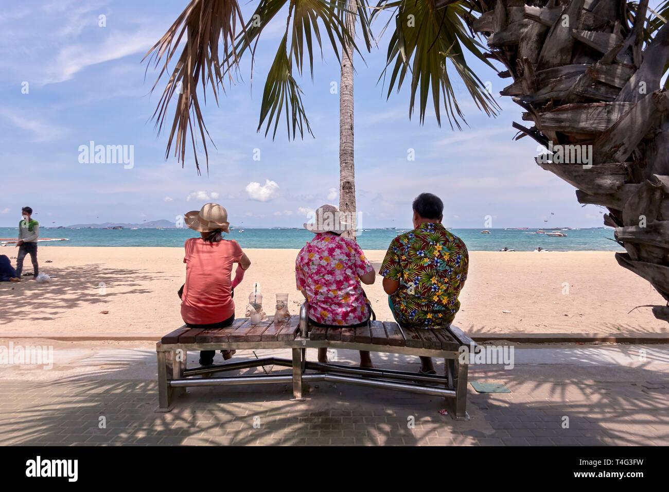 Tres personas. Hombre y dos acompañantes sentados en un banco y con vistas al mar en la playa de Pattaya, Tailandia, el sudeste de Asia Imagen De Stock