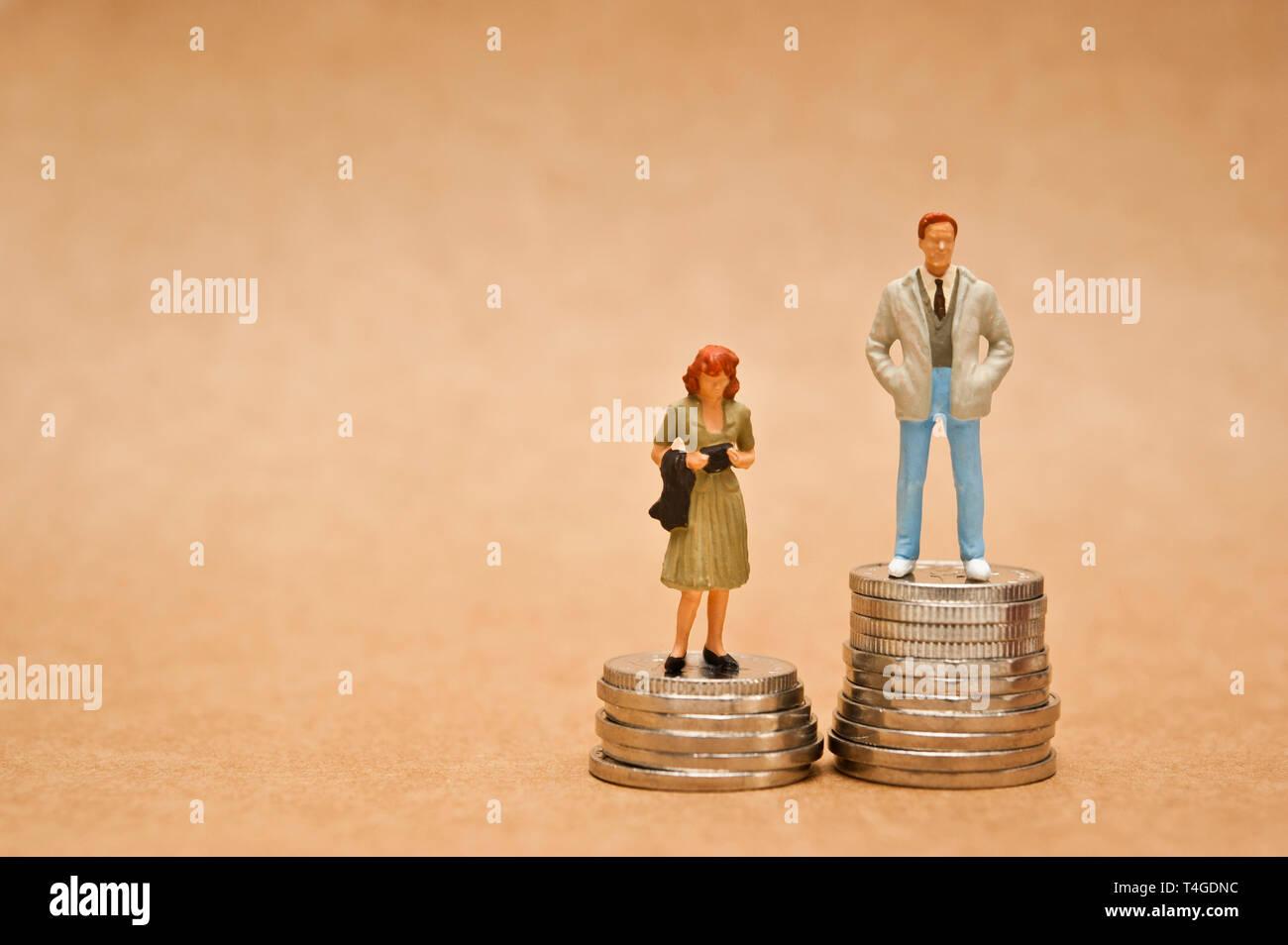 El hombre y la mujer en pie de figurillas en monedas, la brecha salarial entre los géneros concepto Imagen De Stock