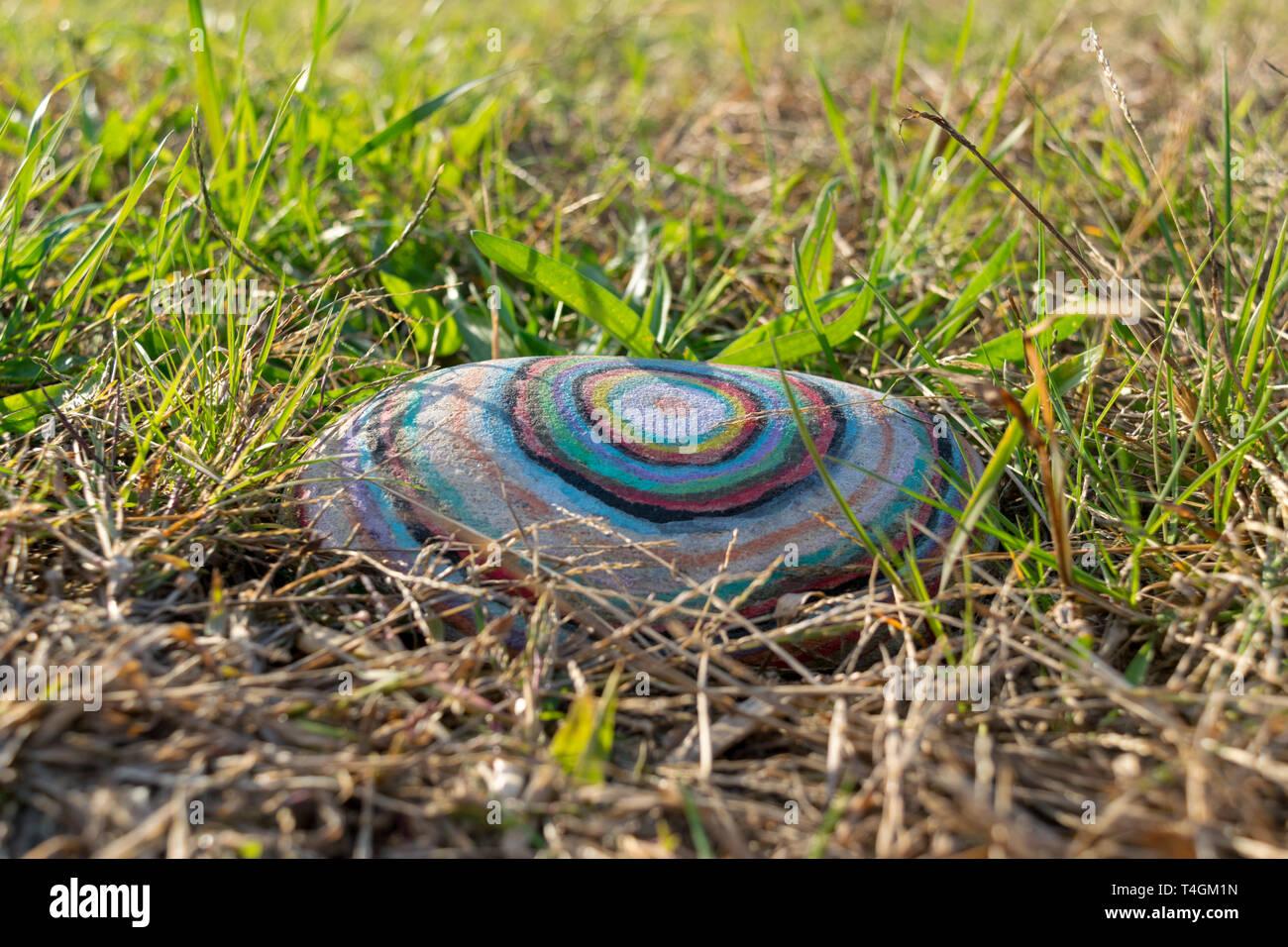 Rock con coloridos círculos pintados acostado en el pasto verde Imagen De Stock