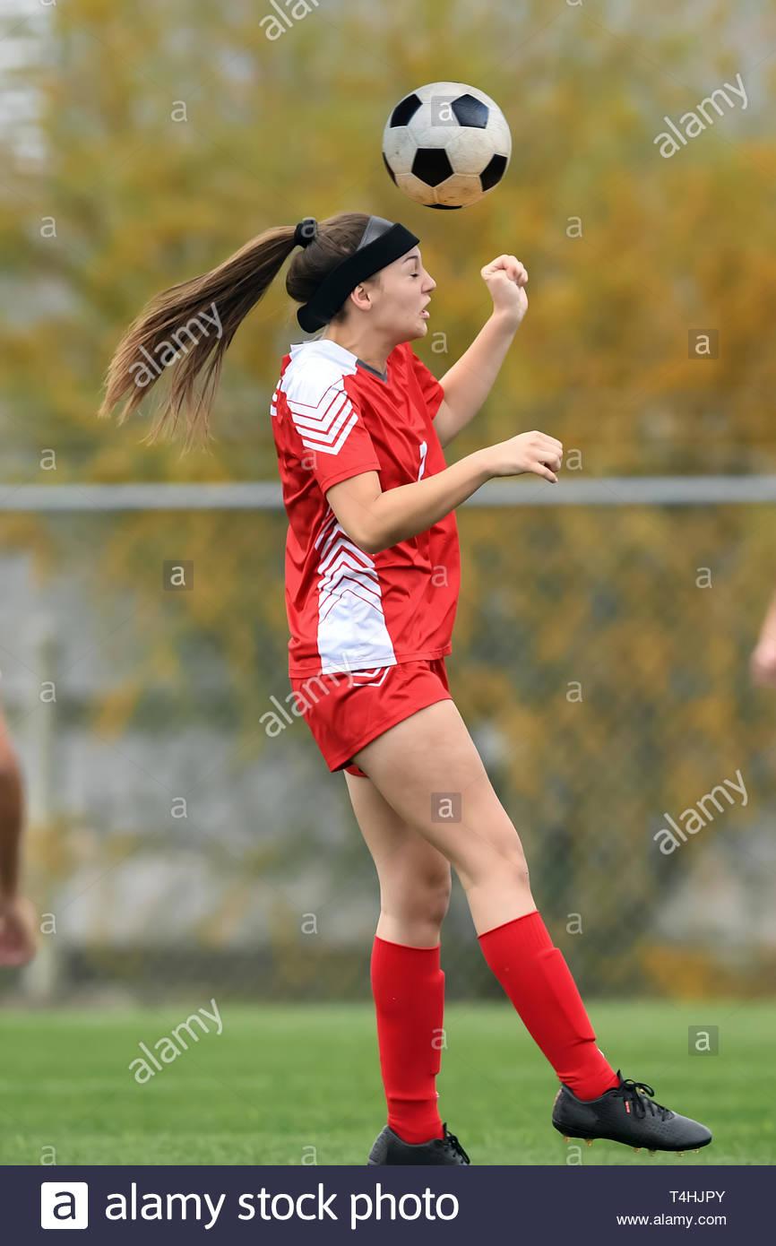 Joven en un uniforme rojo jugando en un juego de fútbol Foto de stock