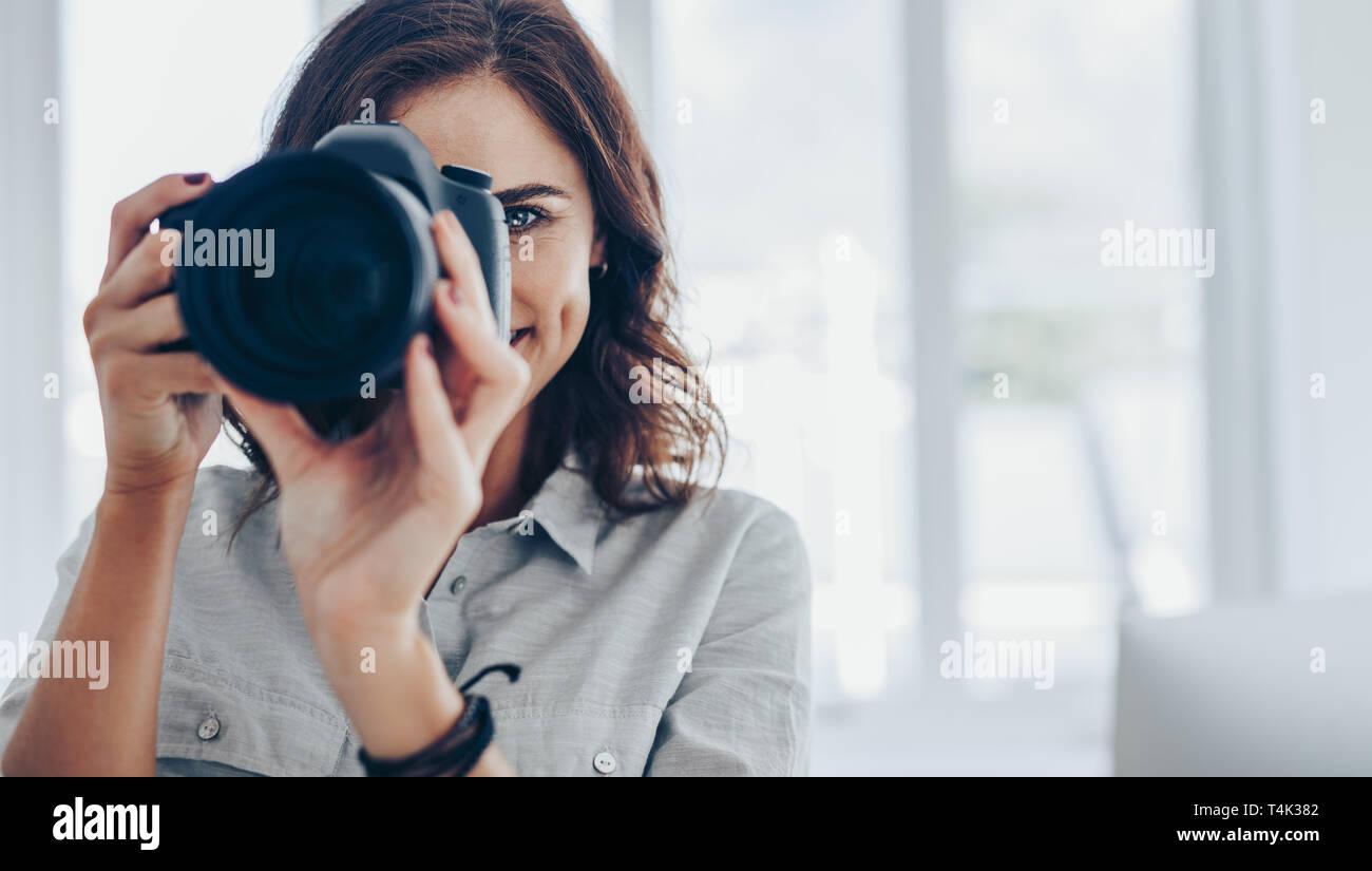 Mujer fotógrafo tomando fotos con su cámara DSLR profesional en interiores. Toma de fotografía femenina en la cámara digital. Foto de stock