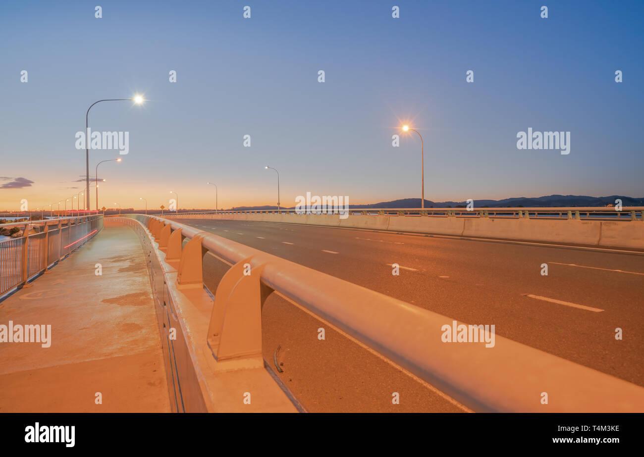 El Puerto de Tauranga Puente ruta de transporte por carretera y vía peatonal y ciclista con resplandor de ciclistas y pasando las luces del vehículo Foto de stock