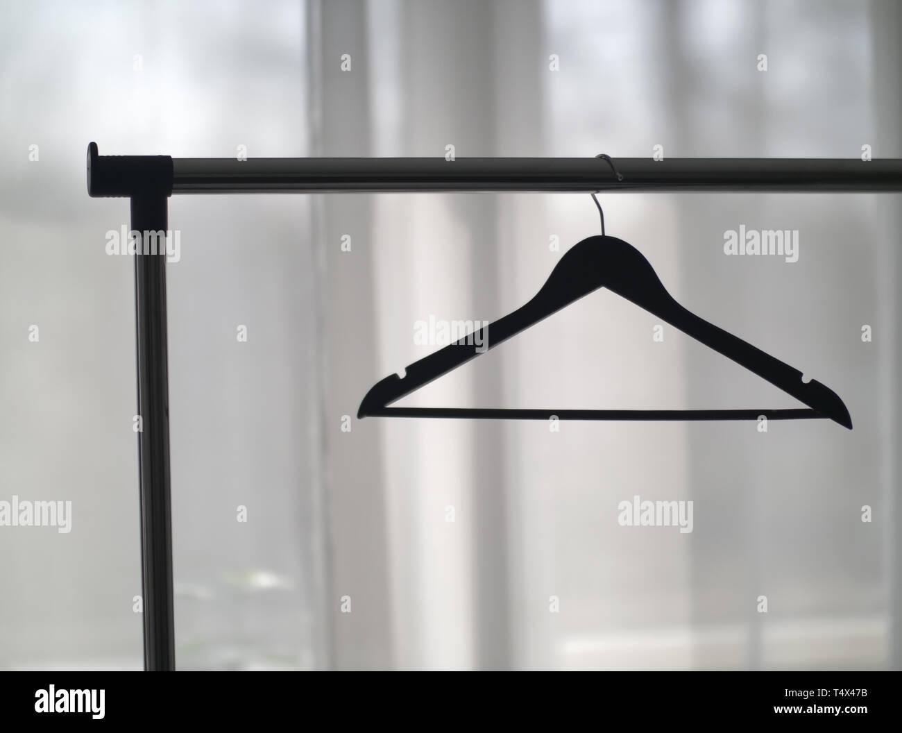 Percha en un riel de metal contra la ventana Foto de stock