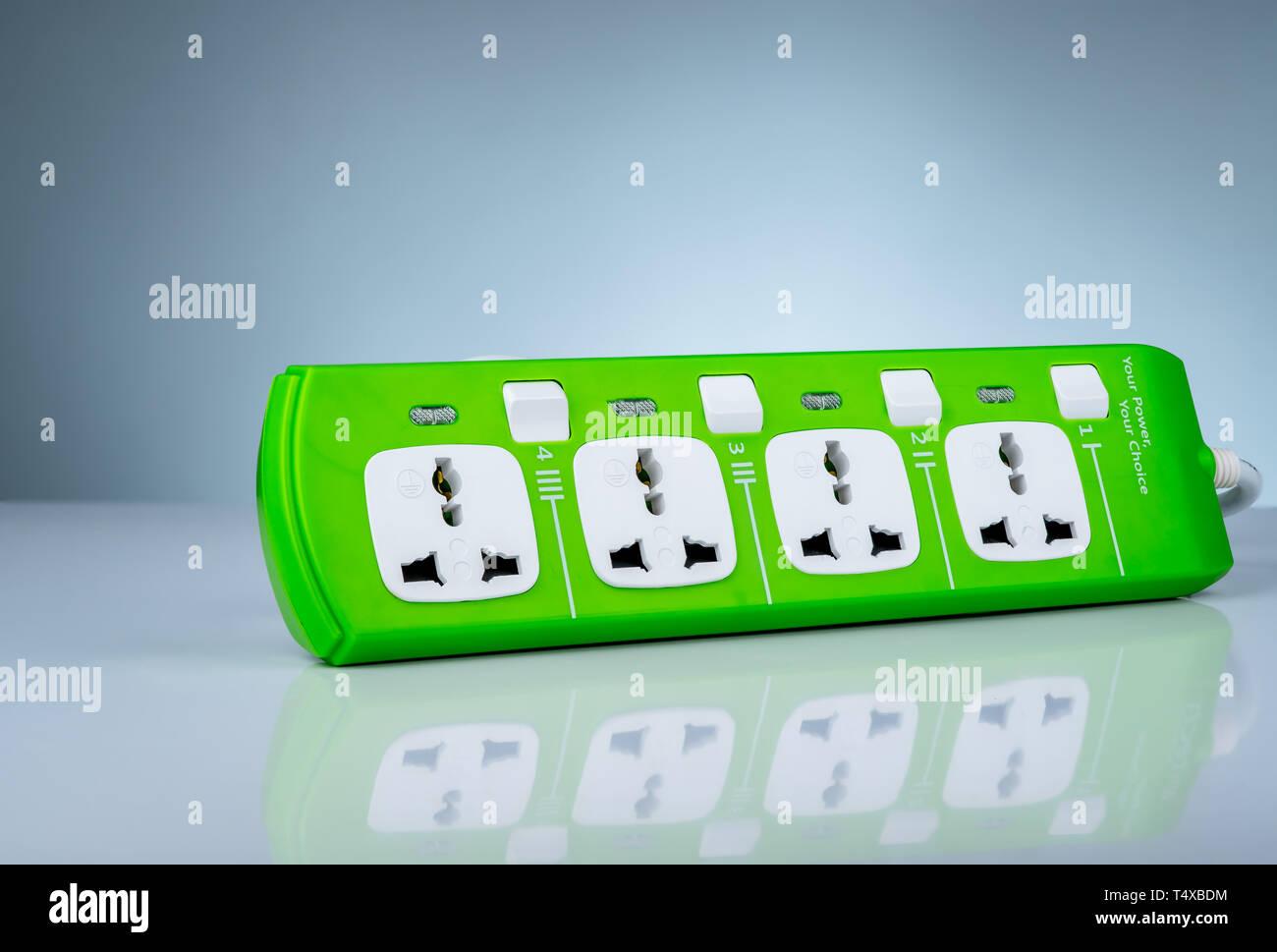 Alta calidad y seguridad regleta con cuatro sockets estándar eléctrico. Enchufe universal verde con protección de sobrecarga. Material resistente al fuego para Foto de stock