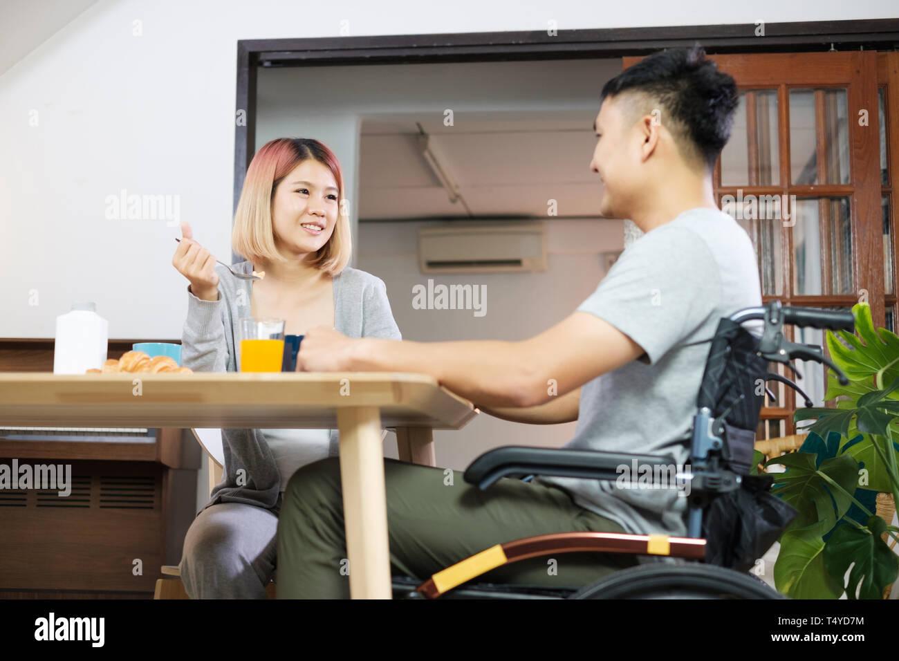 Par de Asia desayuno en casa.esposa sosteniendo la mano y alentar el marido inválido sentado en la silla de ruedas en la mesa de la cocina.pareja en inicio concepto Imagen De Stock